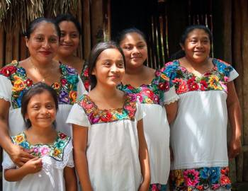 group of young girls with white shirts and floral collars on in mexico