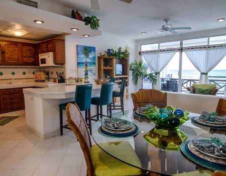 kitchen and dining room at playa caribe rental condo with bright decor and white flooring, walls, and tiling